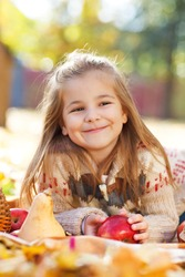 Adorable little girl with autumn leaves and apple in the beauty park