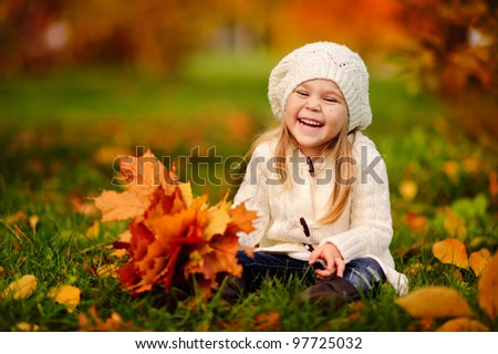 adorable little girl with autumn leaves in the beauty park #97725032