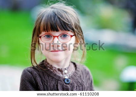 Adorable little girl with beauty blue eyes in glases