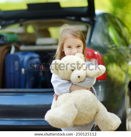 Adorable little girl with big teddy bear leaving for a car vacation with their parents
