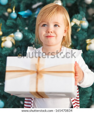Adorable little girl with Christmas present under the Christmas tree