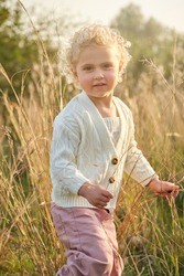 Adorable little girl with curly hair wearing white sweater standing on verdant grassy lawn in sunny summer countryside and looking at camera