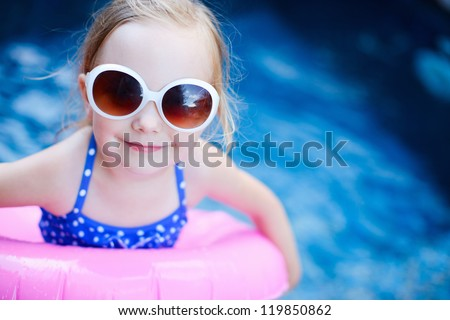 Adorable little girl with inflatable ring at swimming pool - stock photo