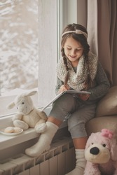 Adorable little girl, writing letter to Santa, sitting on a window, books and teddy bear around.First snow
