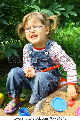 Adorable little girl 2 years old wearing glasses in jeans overalls playing in a sandbox