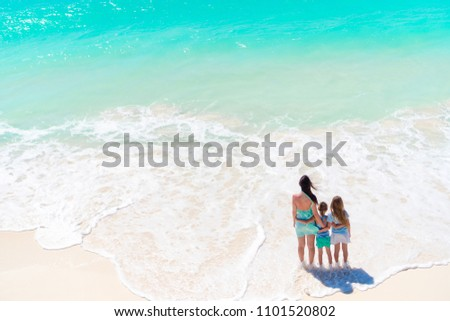 Adorable little girls and young mother on white beach. View of the family and ocean from above