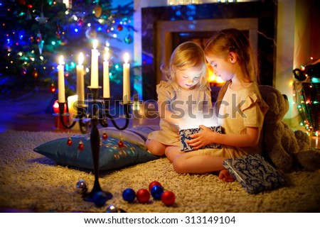 Adorable little girls opening a magical Christmas gift by a Christmas tree in cozy living room in winter