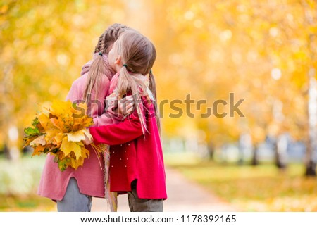 Adorable little girls outdoors on a warm autumn day together. Kids in fall