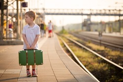 Adorable little kid boy dressed in shorts and polo t-shirt on a railway station, waiting for the train with retro old green suitcase. Ready for vacation. Young traveler on the platform.