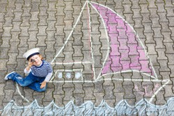 Adorable little kid boy playing with colorful chalks and painting ship or boat picture. Creative leisure for children outdoors in summer, Family, happy childhood,  kids concept