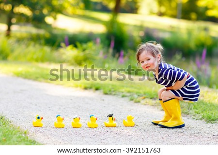 Adorable little kid girl playing in forest playground with yellow rubber ducks. Cute child wearing rain boots. Active leisure with kids. #392151763