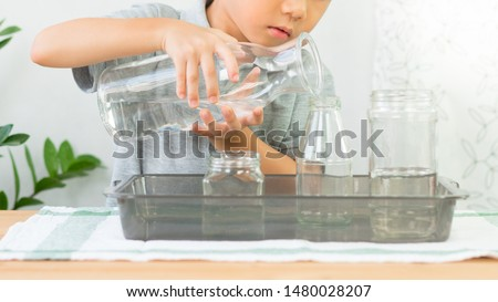Adorable little kindergarten child, boy pours water from glass jar into bottle with care, focus and concentration. Montessori, Child Development Activity, Practical Life Skills, Hand Eye Coordination. ストックフォト ©