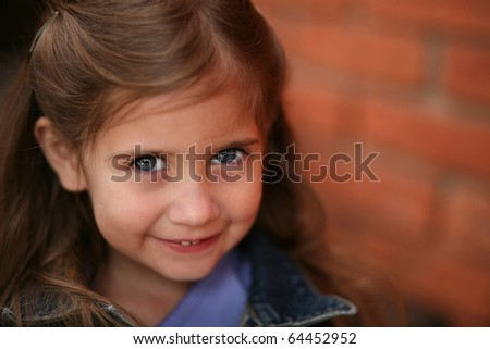 adorable little preschool age girl sitting and smiling #64452952