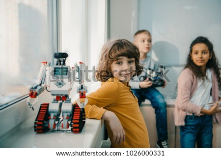 adorable little schoolboy with diy robot on stem education class #1026000331