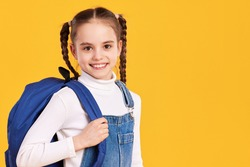 Adorable little schoolgirl with pigtails wearing casual white turtleneck and denim overall carrying backpack and looking at camera with smile against yellow background