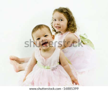 Adorable little sisters in pink dresses on white - stock photo