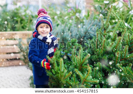 Adorable little smiling kid boy holding christmas tree. Happy child in winter clothes, hat, gloves choosing xmas tree in outdoor shop. Family, tradition, celebration concept