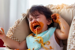 Adorable little toddler child or infant baby crying that don't want eating food on baby chair Cute infant children get hungry and want new food Children get dirty Kid get tantrum Baby is wayward baby