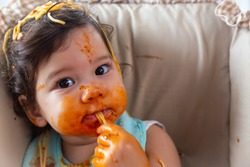 Adorable little toddler girl or infant baby eating delicious spaghetti food with tomato sauce. Funny cute infant girl get hungry and eating food by using hand. Mix race daughter get dirty all body