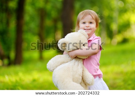 Adorable little toddler girl with a big teddy bear having fun in summer park on be?utiful sunny day