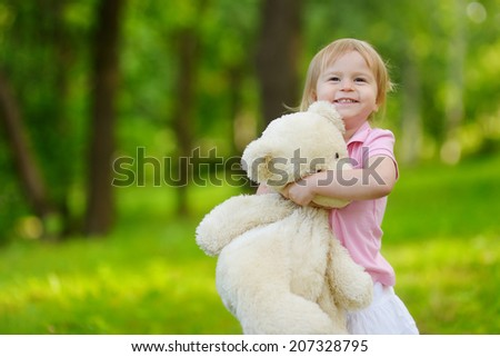 Adorable little toddler girl with a big teddy bear having fun in summer park on beautiful sunny day