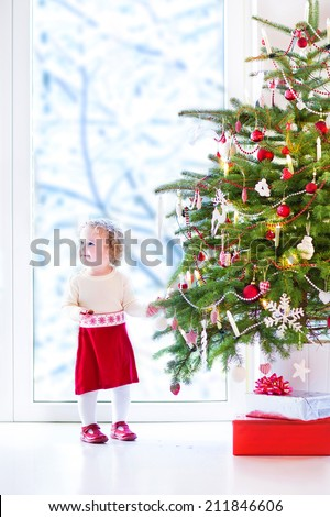 Adorable little toddler girl with curly hair in a warm knitted dress decorating a beautiful Christmas tree at a big window with a view of a snowy garden