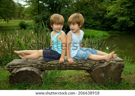 Adorable Little Twin Brothers Sitting on a Wooden Bench, Smiling and Looking at Each Other Near the Lake at Summer
