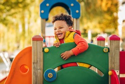 Adorable little 1-2 year old toddler boy having fun on playground, child wearing orange hoody jacket and yellow vest