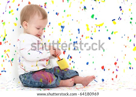 Adorable 10 month old baby girl playing with paint in paint splattered room.