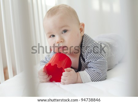 adorable 7 month old baby posing in white crib with a red toy