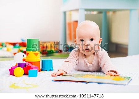 Adorable 6 months old baby looking and reading a book. Baby playing with colorful toys at home. Happy child playing and discovery. Early development, learning and education of kid
