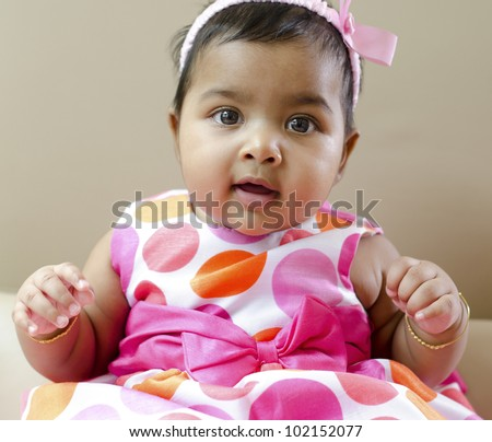 Adorable 6 months old Indian baby girl sitting on sofa