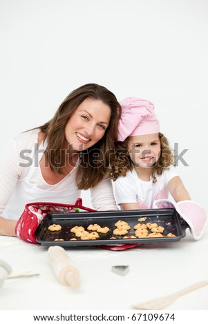 Adorable mother and daughter showing a plate with biscuits to the camera