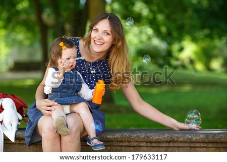 Adorable mother and little baby girl having fun together in summer park