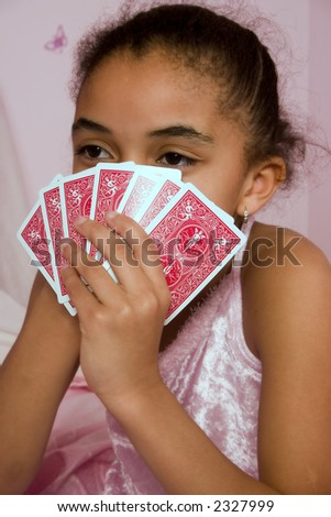 Adorable mulatto girl playing cards with her friends at a slumber party.