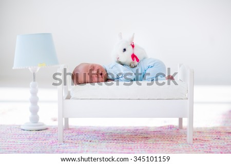 Adorable new born kid sleeping in a white toy bed with real rabbit. Nursery for newborn baby. Cute boy taking a nap in sunny bedroom with his bunny. Family with children and pets. Child and animal.