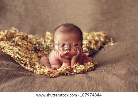 Adorable newborn baby boy on elbows
