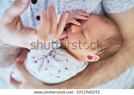 Adorable newborn baby girl sleeping on her father's chest and sucking his finger
