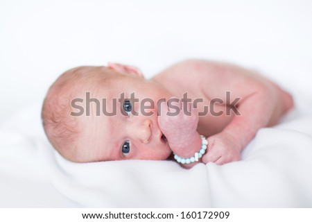 Adorable newborn baby on a white blanket