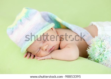 adorable newborn baby with funny cap on her head sleeping on stomach
