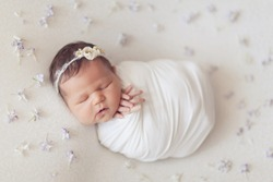 Adorable newborn 10 day old baby girl on white background with flowers