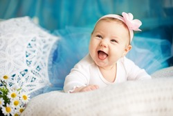 Adorable newborn girl laughing on white plaid with flower on head and blue ballerina skirt