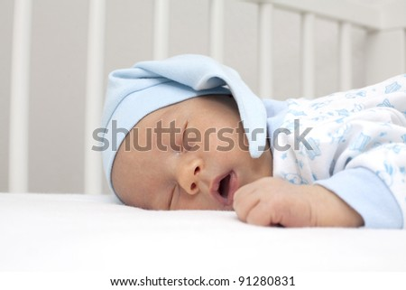 adorable newborn in funny hat is sleeping in his crib