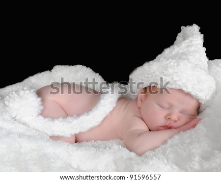 Photo of adorable newborn in hat sleeping on a white blanket.isolated on black