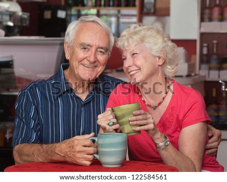 Adorable older couple sitting together in a bistro