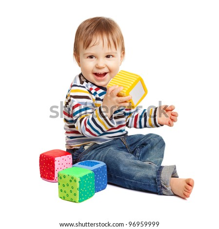 Adorable one year old child playing with toy cubes, isolated on white