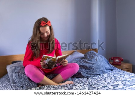 Adorable part Japanese part caucasian little girl with long black hair in red dress and pink leggings sitting cross-legged in bed reading from a notebook #1461427424