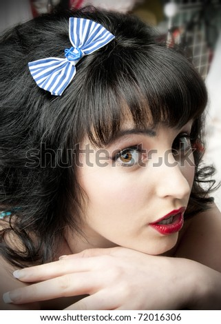 Adorable pinup model wearing blue anchor hair bow