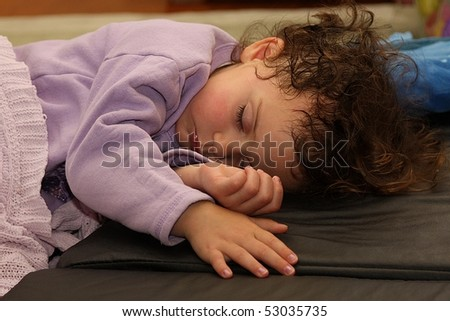 Adorable portrait of kid sleeping on black mattress