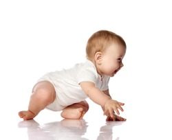 Adorable positive little baby infant in white cotton body and barefoot trying to creep on floor, smiling and looking aside over white background. Happy childhood concept